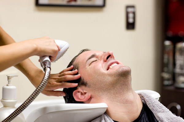 Man getting his hair washed at a beauty salon.