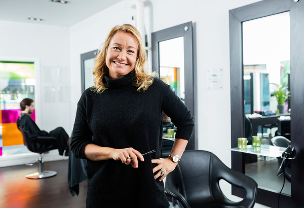 Hair stylist dressed in black smiling.