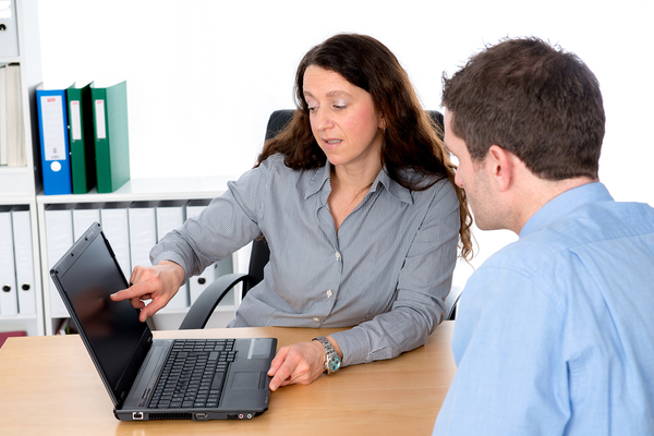 Woman pointing to a mans laptop screen