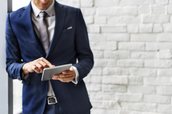 Man wearing a suit and leaning against a wall using his tablet.