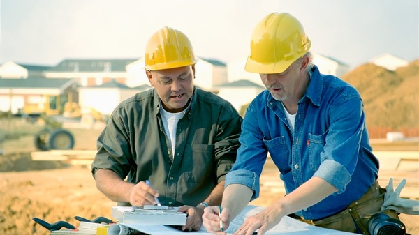 Two contractors with yellow hardhats looking at plans