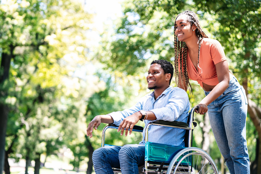 Woman pushing a man in a wheel chair outside.