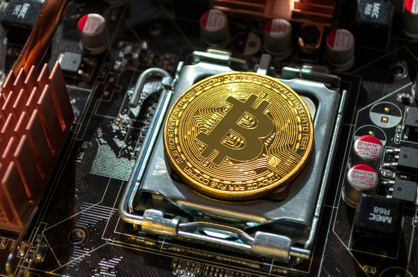 Gold coin with a bitcoin symbol on top of a computer motherboard.