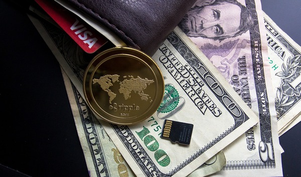 Paper money, a leather wallet and a gold coin with the ripple logo.