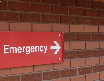 An emergency sign against a brick wall
