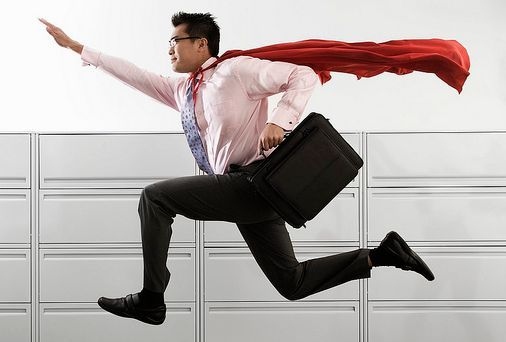 A businessperson leaping into the air, a cape flying from their neck