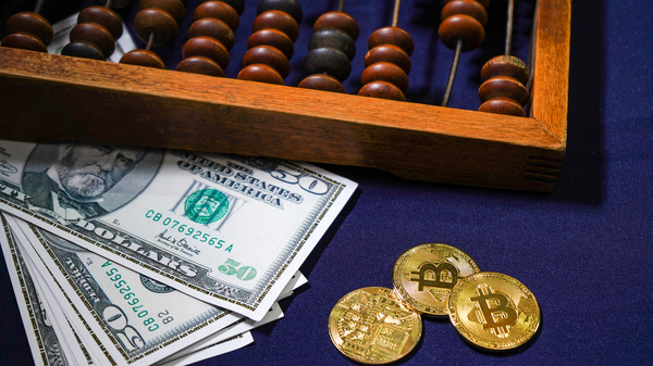 Paper money, gold coins with bitcoin symbols and an abacus.