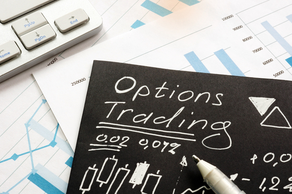 Person writing on black paper with white ink options trading information.