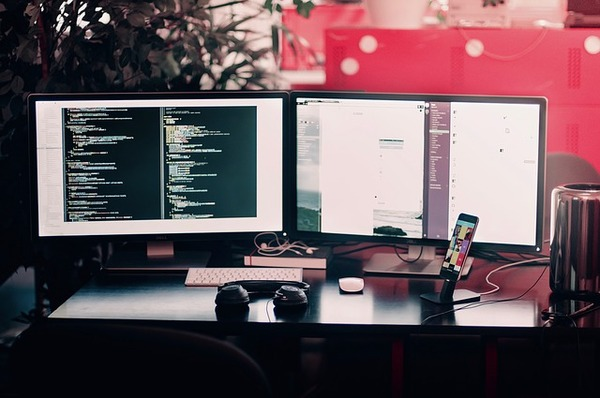 Two computer monitors on a desk.