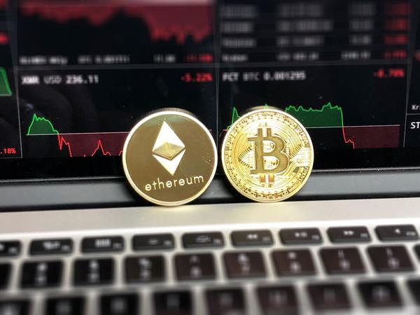 Gold coin with ethereum logo, and gold coin with bitcoin logo.
