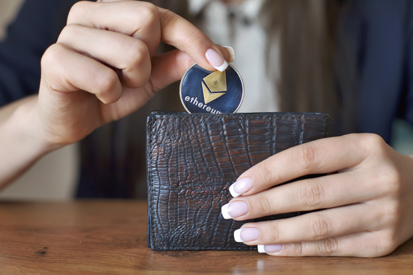 Placing a gold coin with ethereum logo into a wallet.