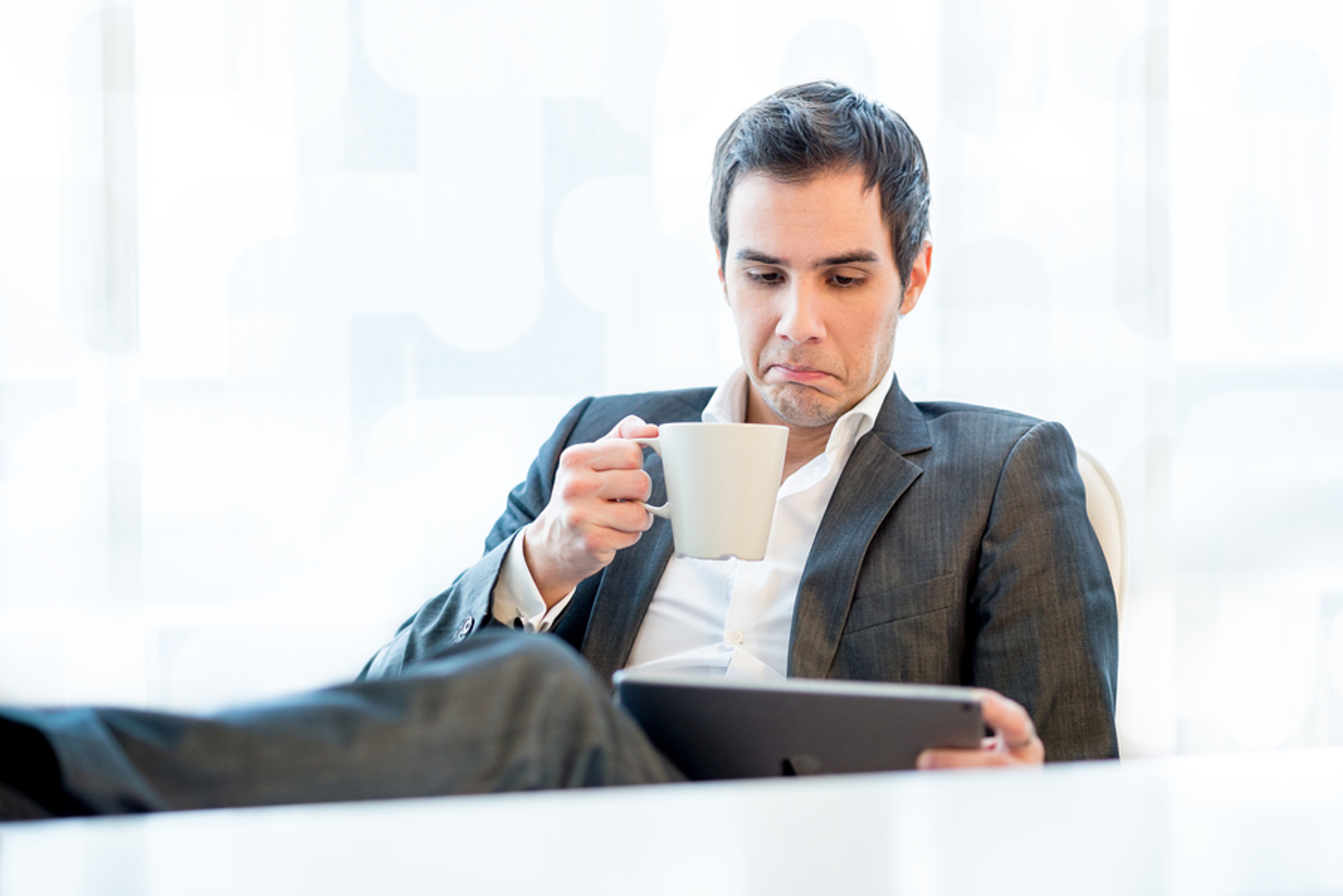 Man looking at his tablet while drinking a coffee.