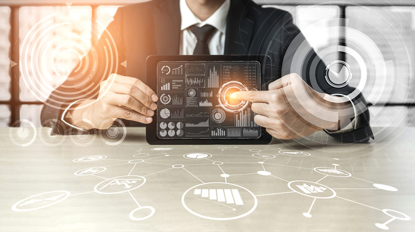 Data analytics image Man pointing to a circle chart on a tablet.