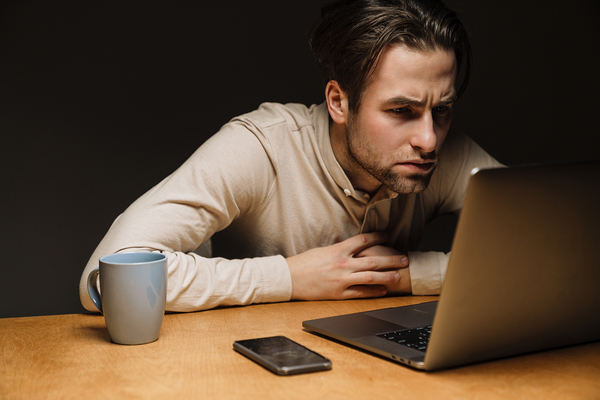 Data Quality Metrics image 1 - Man looking intently at his laptop screen.