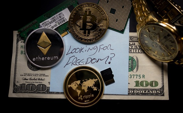 US 100 dollar bill surrounded by cryptocurrency gold and silver coins.