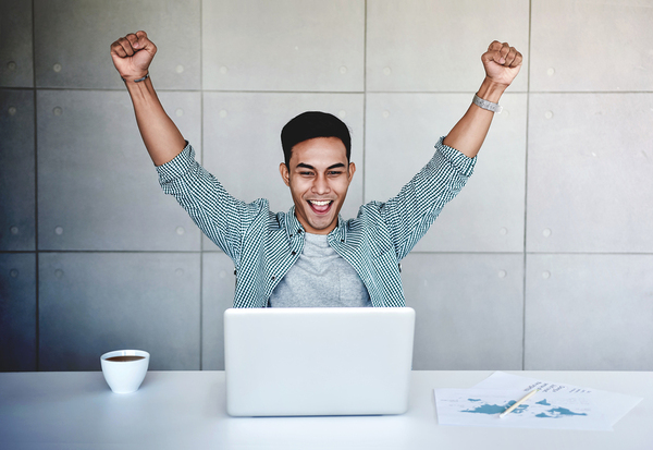 Man raising his hands up in triumph in front of a laptop computer.