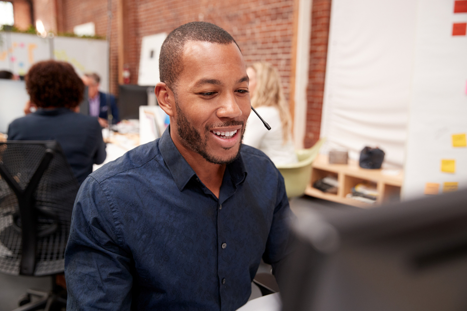 Smiling man in front of a desk top computer speaking into a headset.