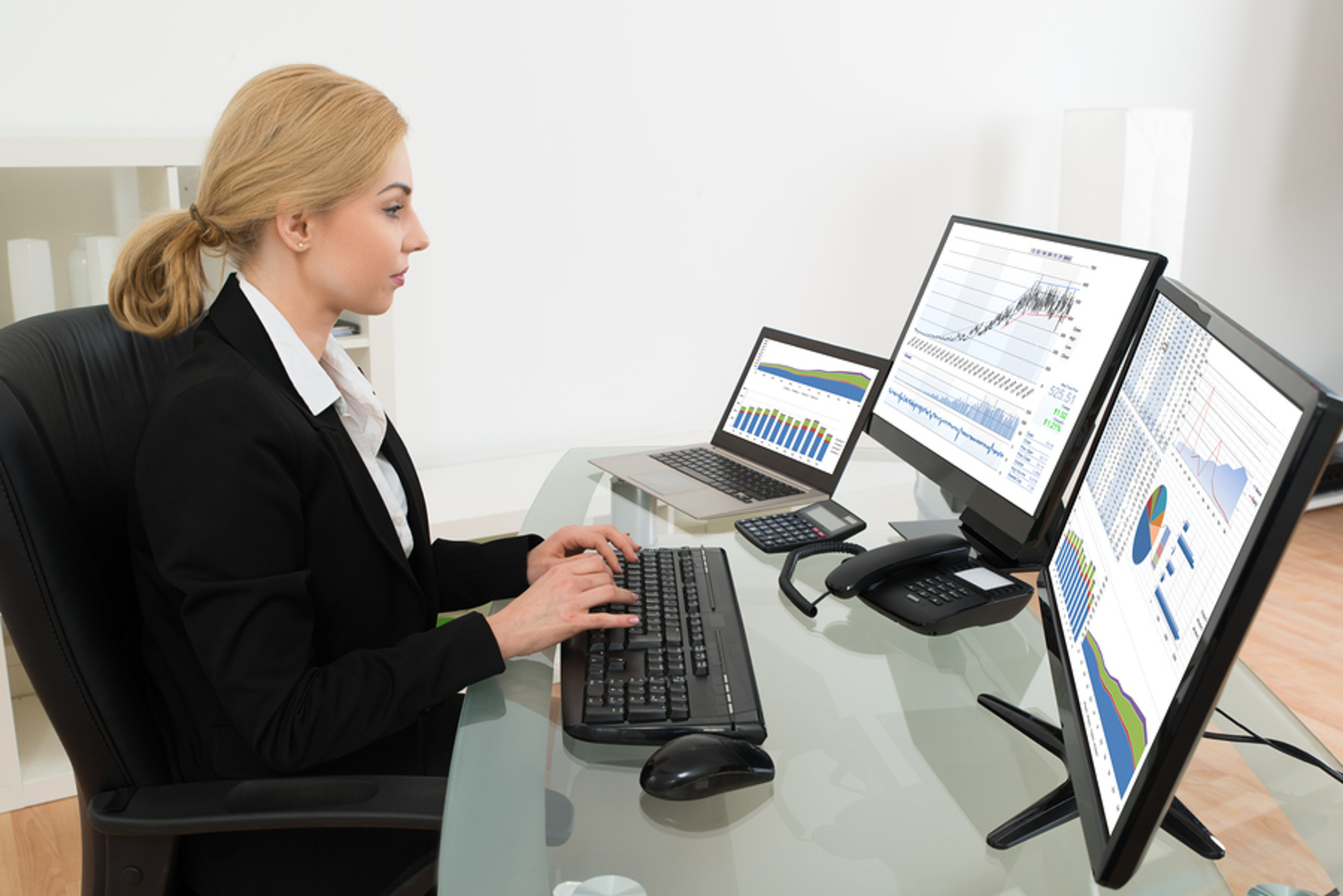 Woman typing on a desktop computer keyboard.