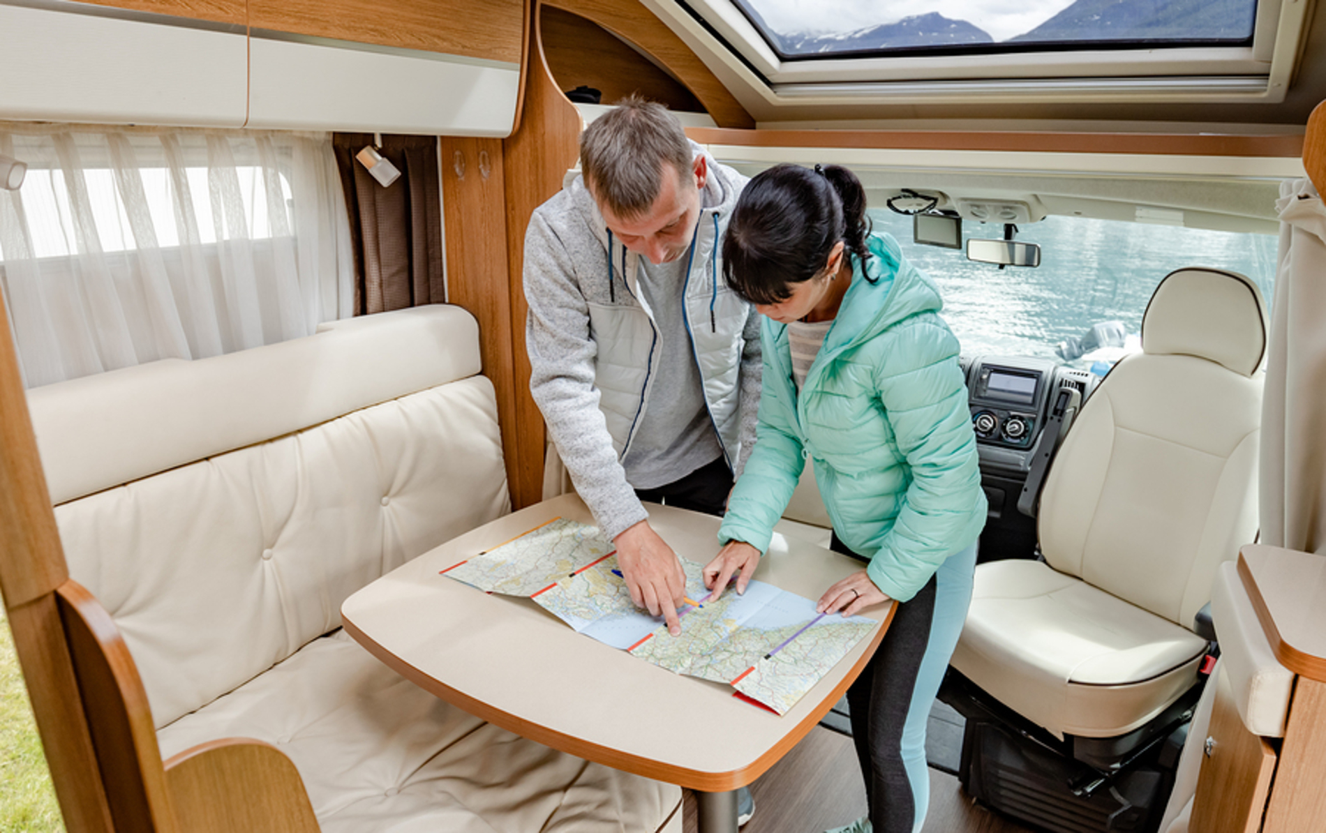 Couple looking at a map inside a rv.