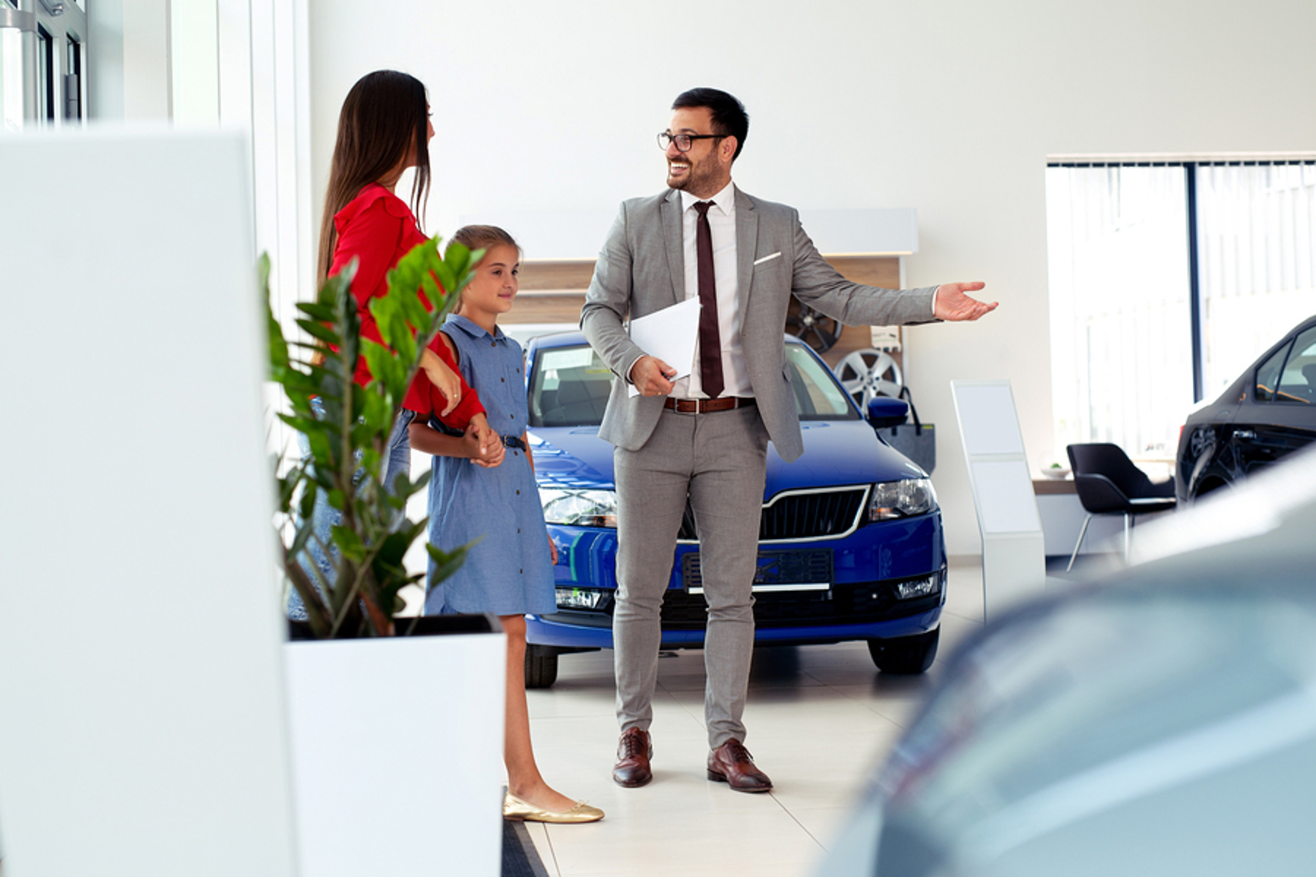 Mother and daughter talking with a car salesman.