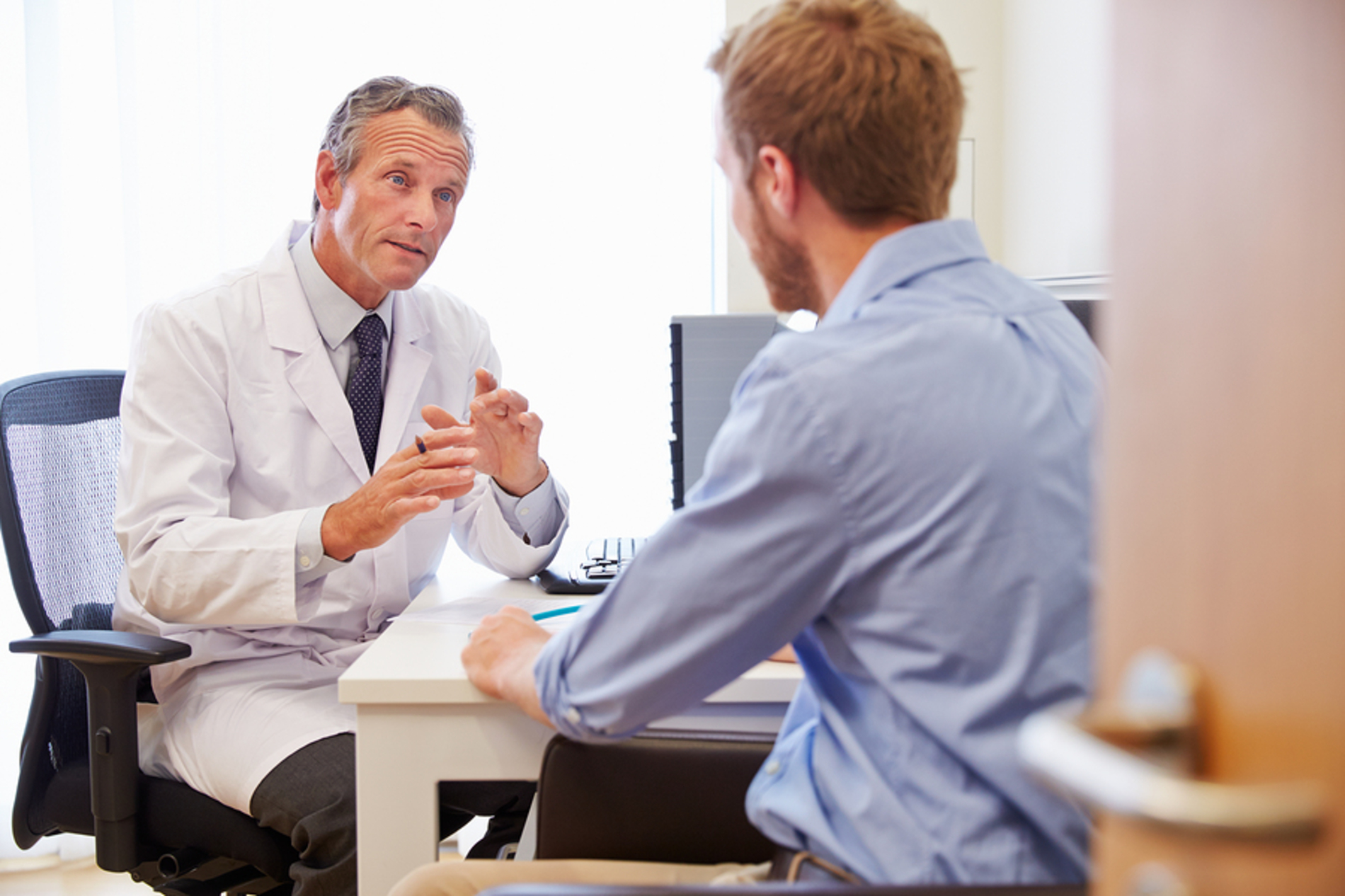 Medical doctor discussing information with a male patient.