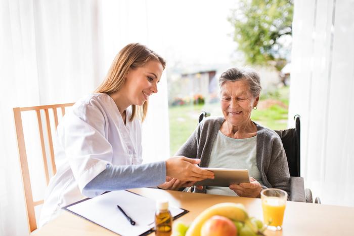 Caregiver helping an elderly woman sitting in a wheelchair.