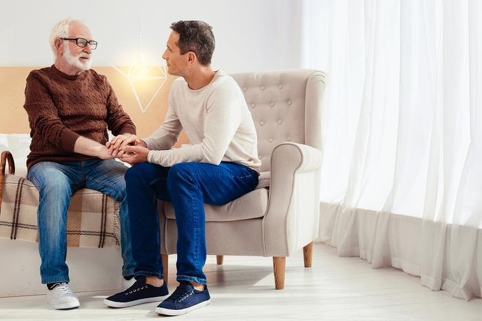 Older gentleman sitting with a caregiver.