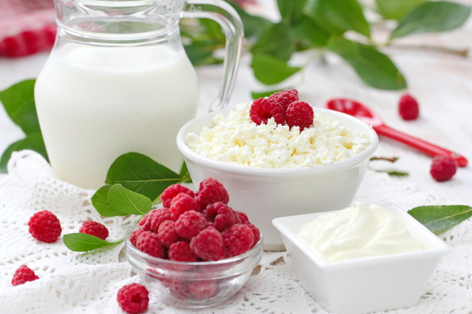 Glass jug of milk and bowl of raspberries.