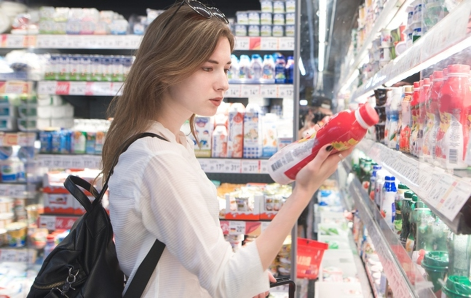 Woman reading a drink label in a grocery store.