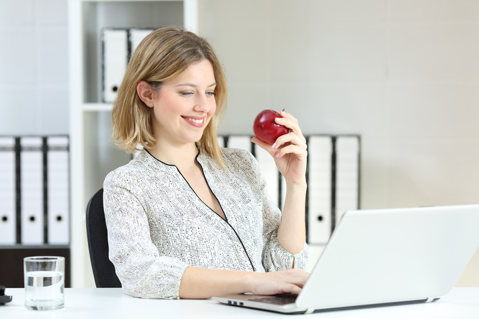 Woman sitting at her desk woking on a laptop eating an apple.