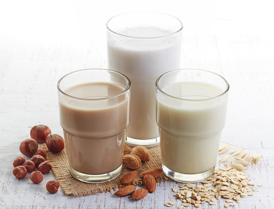 Three glasses of different milks, soy, coconut and flax.