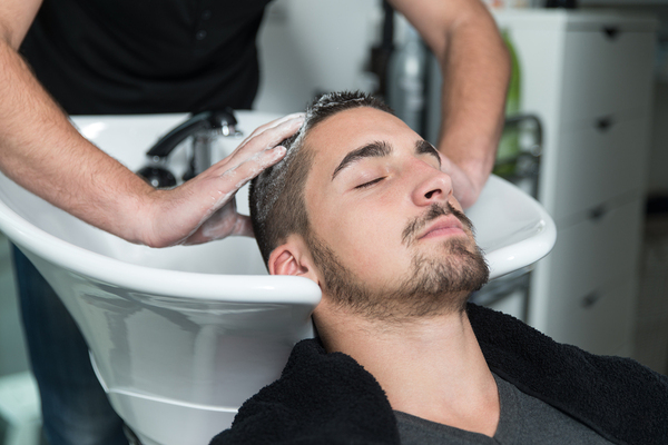 Man getting his hair washed in a salon.