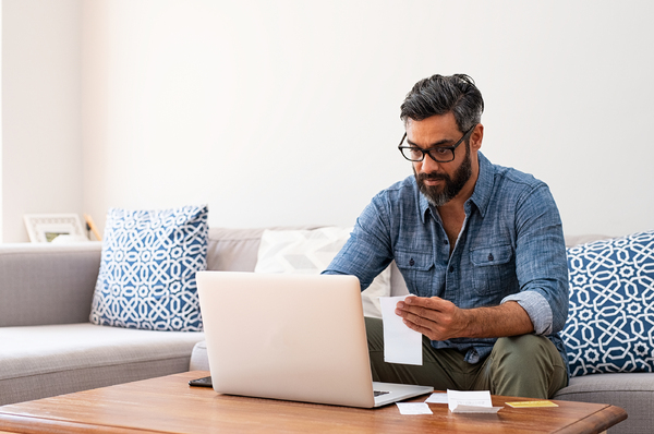 Man sitting on his couch looking at his computer screen while holding a document.