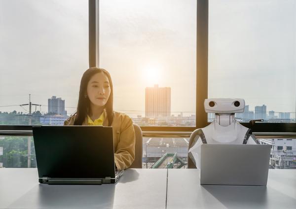 Woman sitting next to a robot.