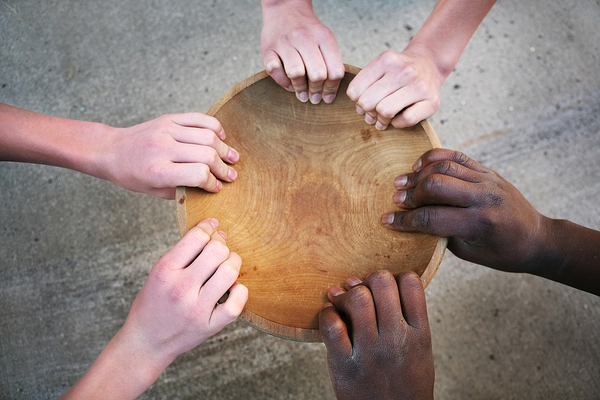 Wooden bowl being held by three sets of hands.