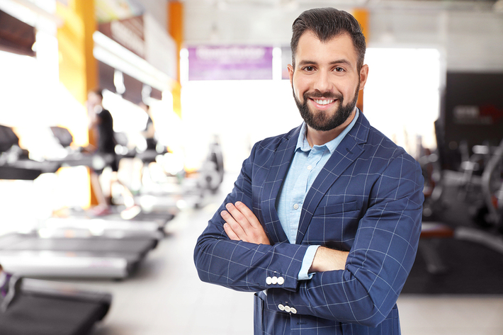 Man in a business suit smiling at a gym.