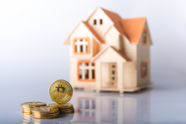 Miniature model of a home with gold coins that have bitcoin symbols.