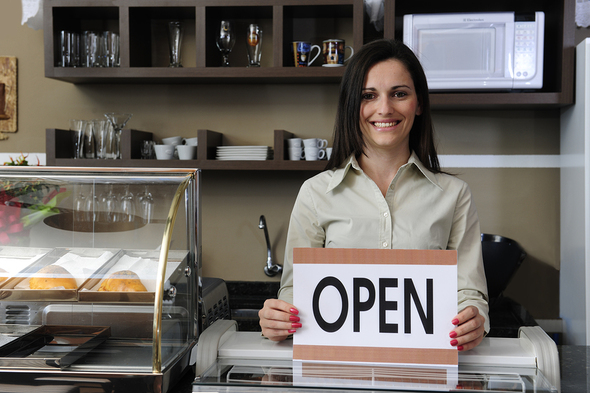 Woman holding an open sign in her shop.