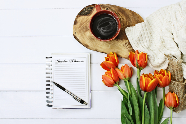 Tabletop with coffee, flowers and notebook with pen.