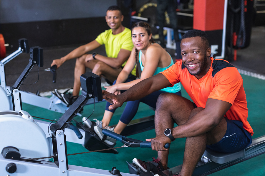 Group of people exercising on rowing machines.