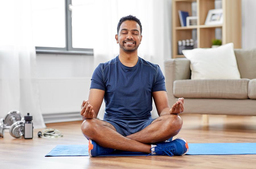 Man sitting on the floor meditating.