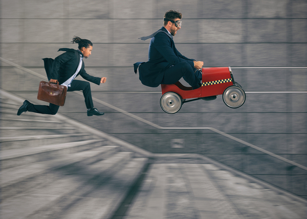 Man in a child's go cart going down concrete stairs, with a man running behind holding a briefcase.