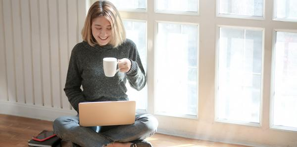 Smiling woman holding a cup of coffee and looking at her laptop screen.