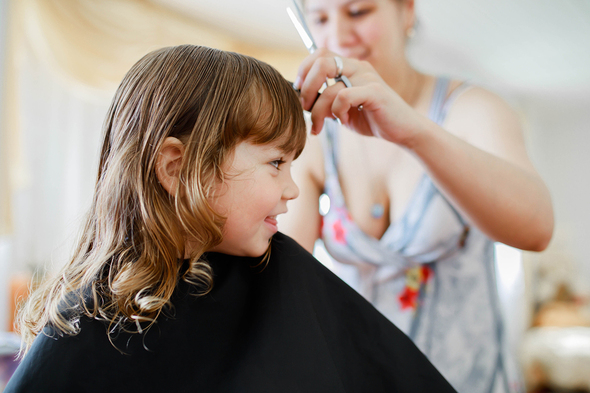 Young girl having her hair styled.