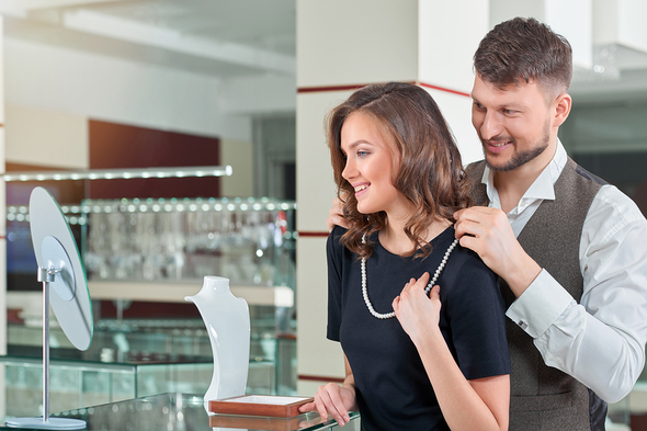 Couple looking at a pearl necklace in a jewelry store.