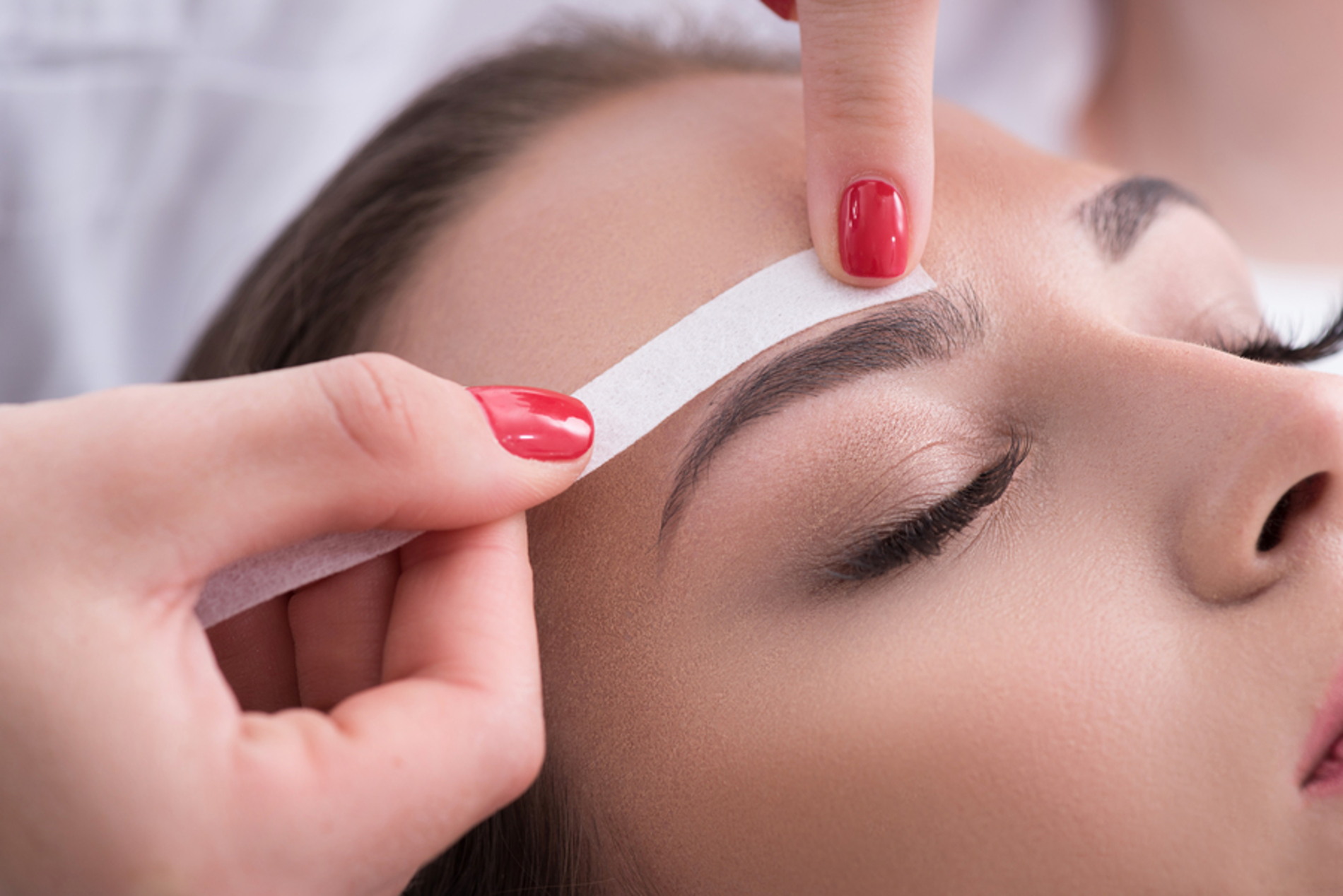 Woman having her eyebrow waxed.