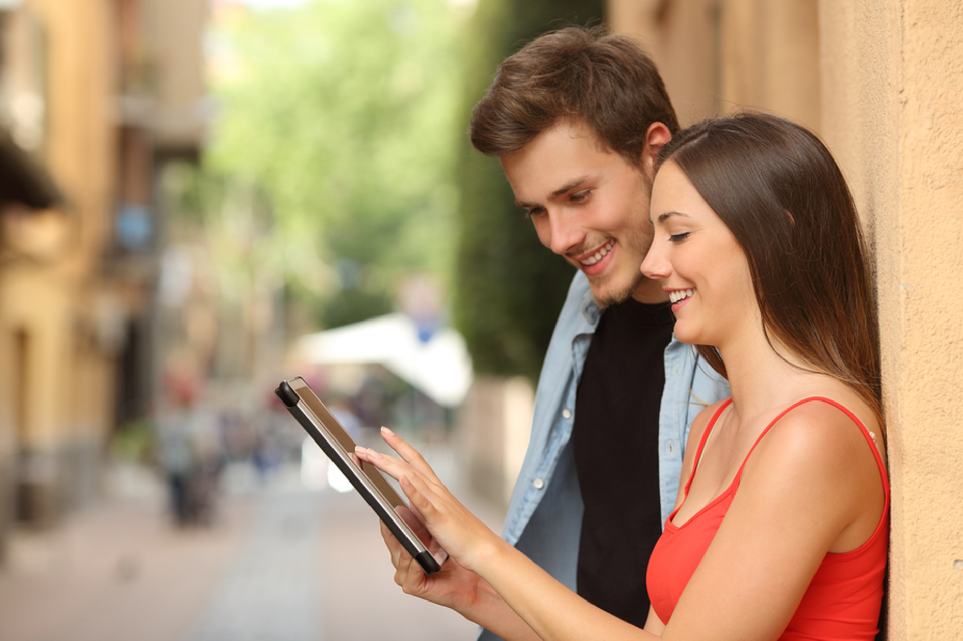 Two people leaning against a well using a tablet to find local businesses.
