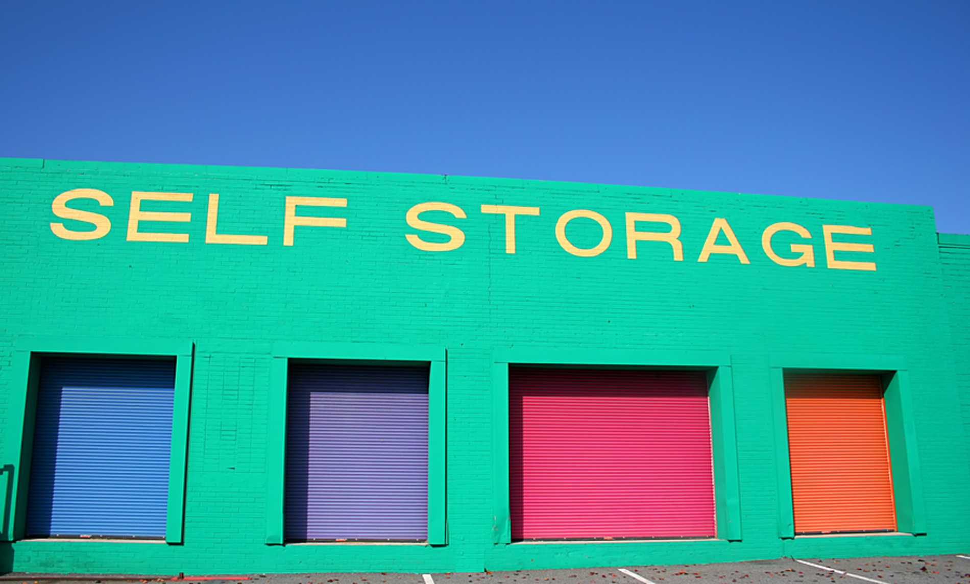 Self storage building with colored doors.