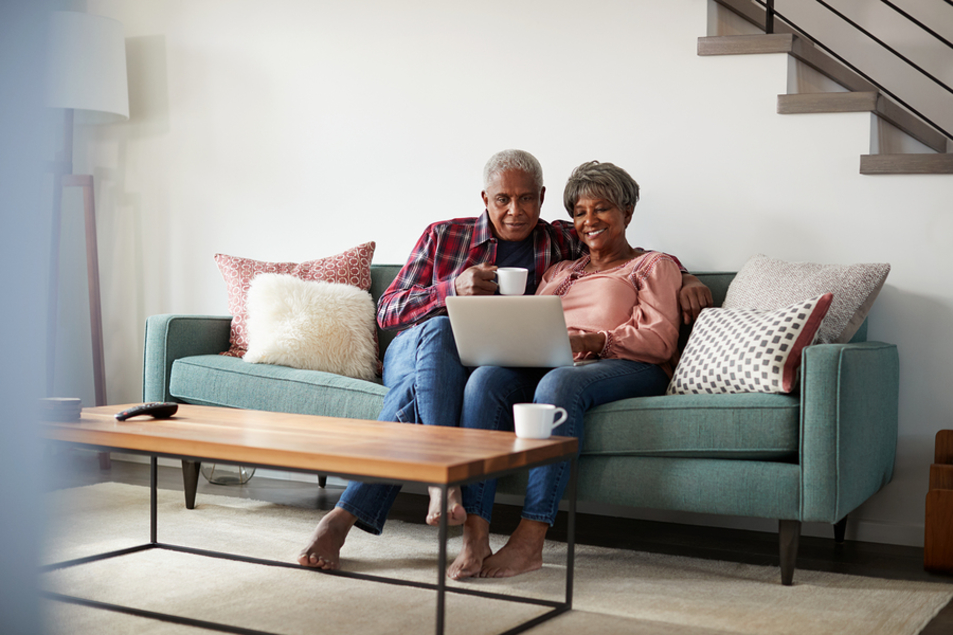 Older couple sitting on a couch looking at a laptop.