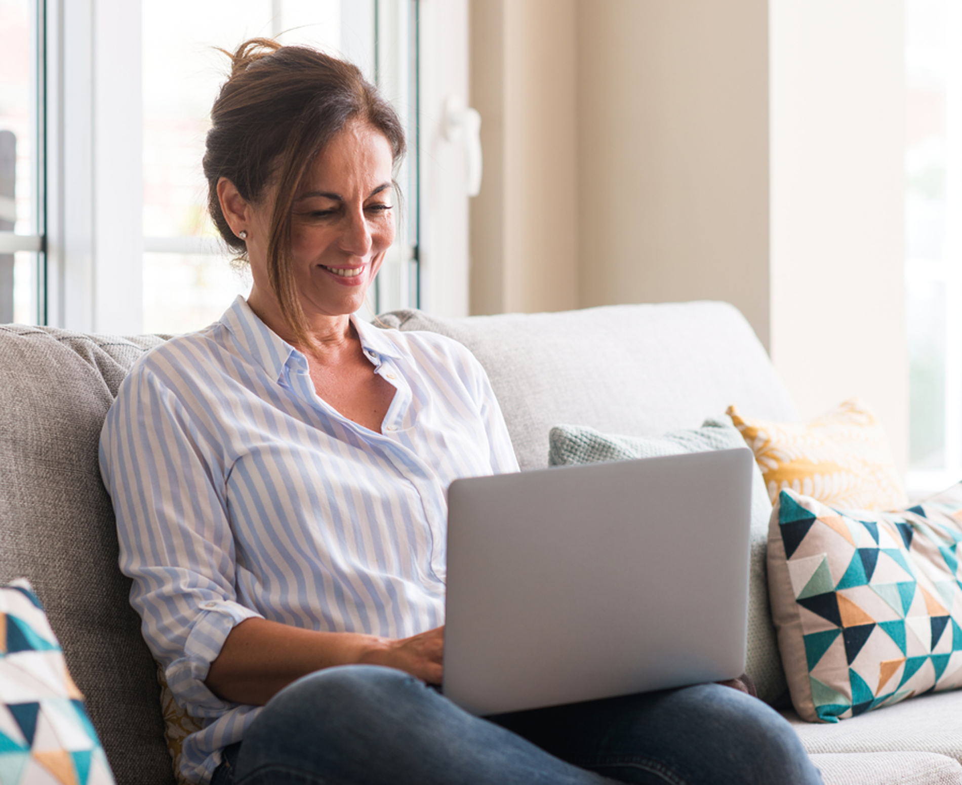 Woman sitting on a couch with her laptop computer.